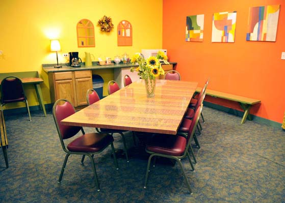 Long Table with 9 chairs, a bench, a desk, and a kitchenette with a microwave and coffee maker at Dance Center Evanston
